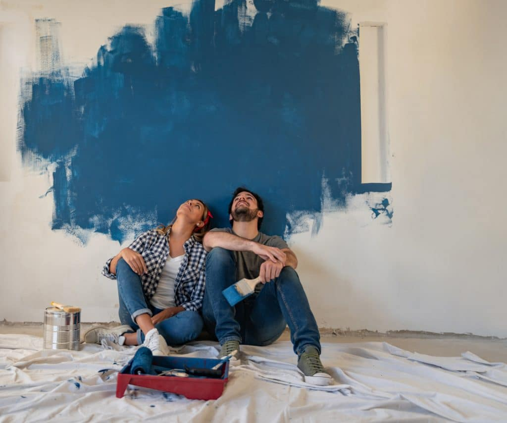 Thoughtful couple painting their house