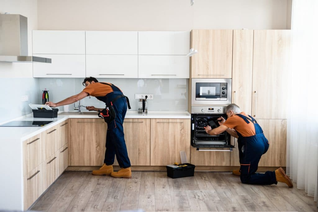Repair. Two handymen, workers in uniform fixing, installing furniture and equipment in the kitchen, using screwdriver indoors. Furniture repair and assembly concept