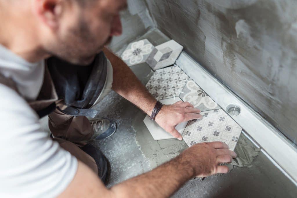 Tiler installing tiles on the bathroom floor