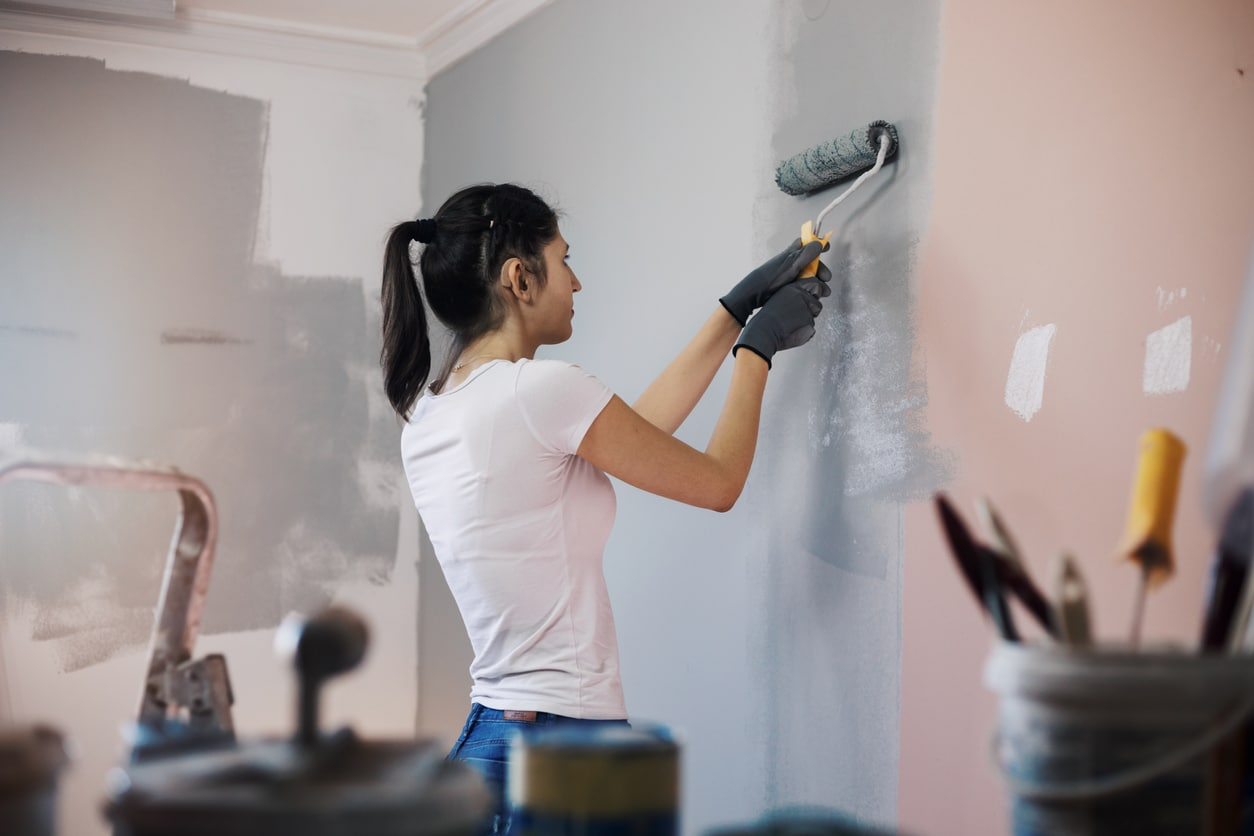 Young woman with hearing aid painting walls