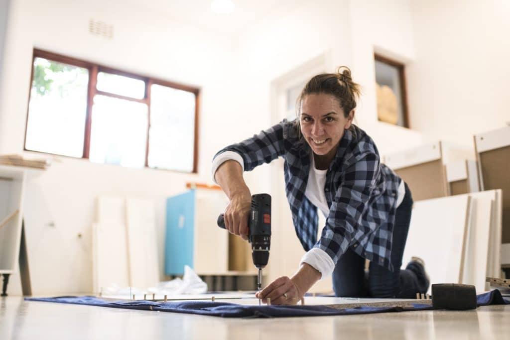 Portrait woman using cordless power tool