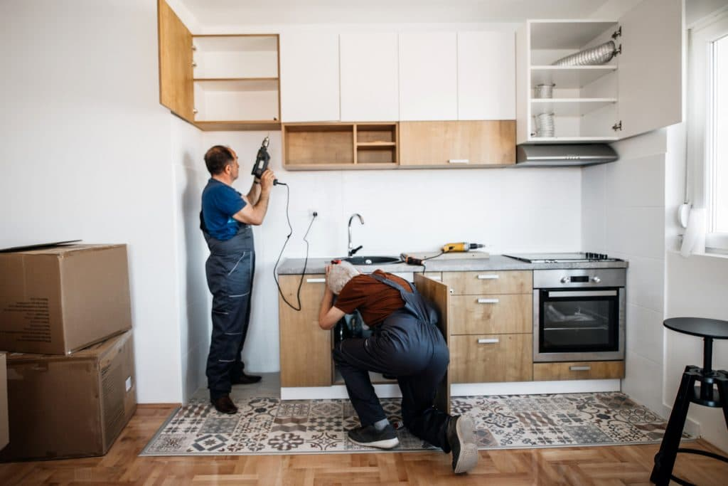 Two Senior Handymen assembling kitchen furniture